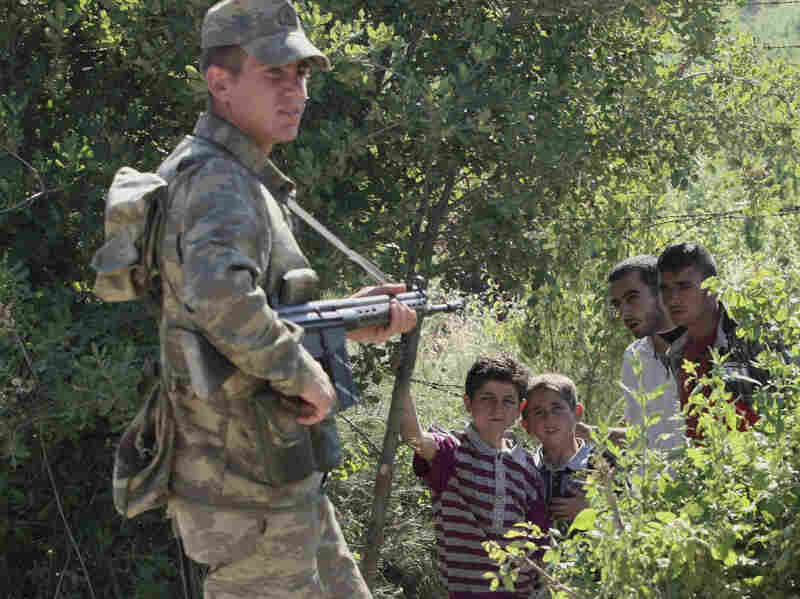 A Turkish soldier stands by as a group of Syrians wait inside Syria for the authorization to enter Turkey near the village of Guvecci in Hatay province on June  9.
