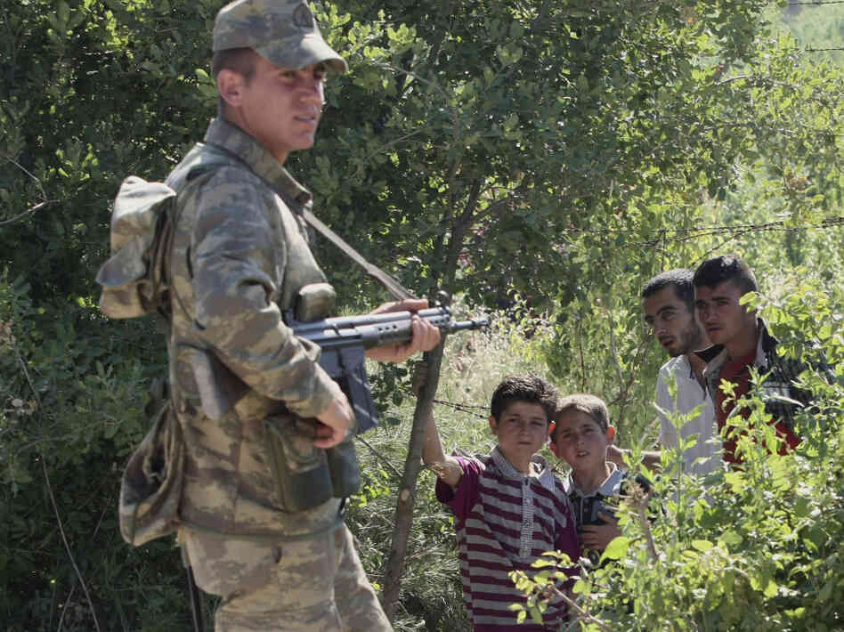 A Turkish soldier stands by as a group of Syrians wait inside Syria for the authorization to enter Turkey near the village of Guvecci in Hatay province on Thursday.