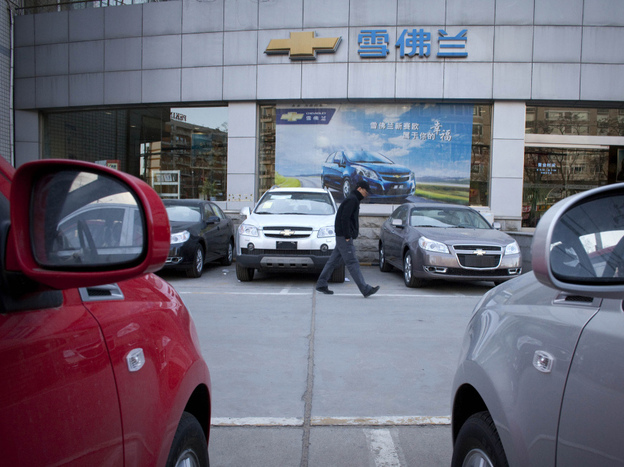 A man walks outside a Chevrolet dealership in Beijing. American automotive companies are expanding, taking brands like Buick and Chevrolet overseas.