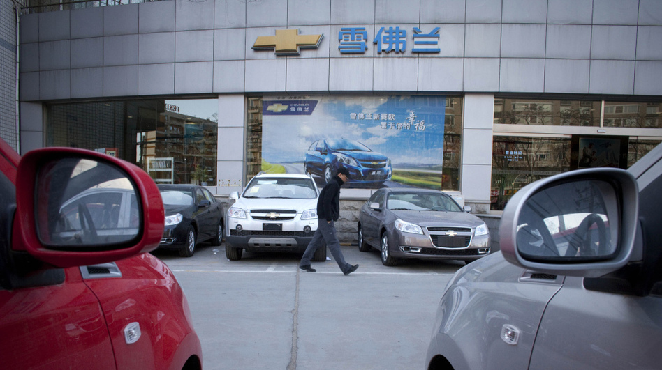 A man walks outside a Chevrolet dealership in Beijing. American automotive companies are expanding, taking brands like Buick and Chevrolet overseas. (AP)