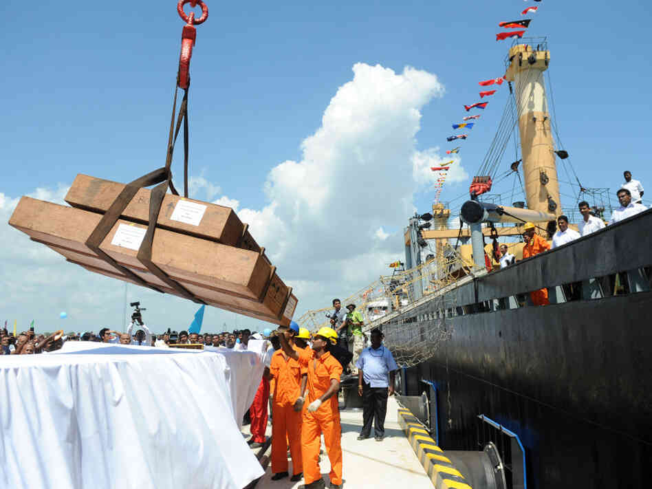 Workers unload cargo from the first vessel to enter the Chinese-funded port in Hambantota, Sri Lanka, in November 2010. China's Export-Import Bank provided 85 percent of the financing for construction of the port.