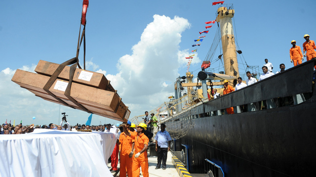 Workers unload cargo from the first vessel to enter the Chinese-funded port in Hambantota, Sri Lanka, in November 2010. China's Export-Import Bank provided 85 percent of the financing for construction of the port. (AFP/Getty Images)