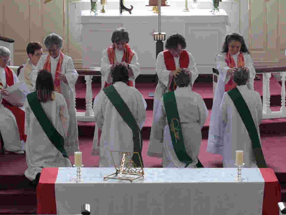 "In the ""laying on of hands"" during the ordination ceremony, the priests place their hands on the candidates before they are officially ordained. The future priests are (from left): Ann Penick, Marellen Mayers, Patricia ""Patti"" LaRosa and  Caryl Johnson."