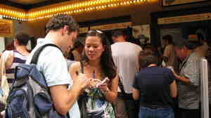 Trent Fucci and Nancy King fill out lottery tickets for The Book of Mormon in front of a Broadway theater. The play has been sold out since previews.