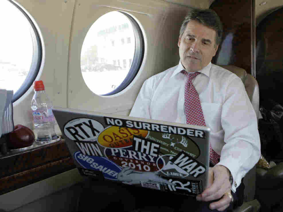 Texas Gov. Rick Perry  looks at his laptop aboard a jet in Addison, Texas, April 12, 2011.