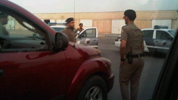 Saudi policemen surrounding the cars of women who drove. (@Maysa_M)