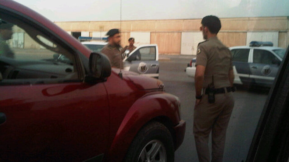 Saudi policemen surrounding the cars of women who drove. (@Maysa_M)