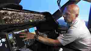 Pilot Gregg Pointon shows off the cockpit of a Boeing 787 flight simulator. GPS navigation is the basis for a new air traffic control system the government plans to build, but a company's plan to expand broadband Internet could interfere with GPS signals.