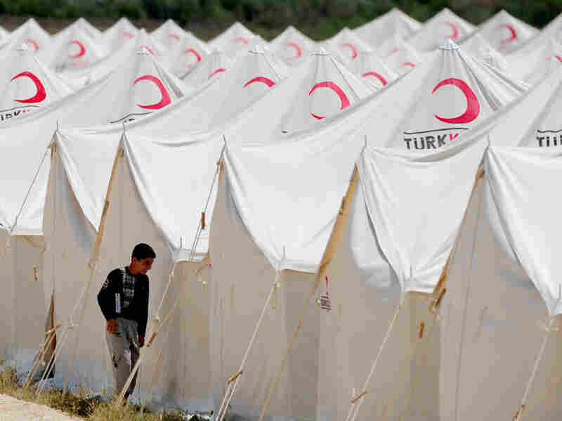 A Syrian refugee boy stands in front of a tent at the Boynuyogun Turkish  Red Crescent camp in the Altinozu district of Hatay, near the Syrian  border.