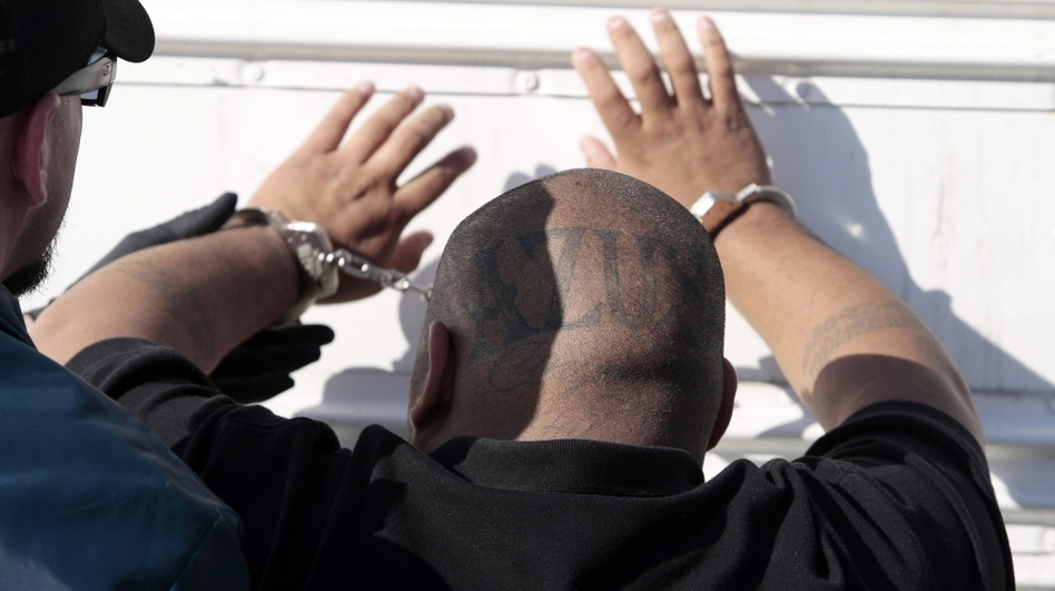 U.S. Marshals deputies restrain a suspected member of an Azusa, Calif., gang after a raid in Irwindale on June 7. The Latino gang conspired to rid the Southern California city of its black residents through threats and violence dating back to the early 1990s, according to an indictment.