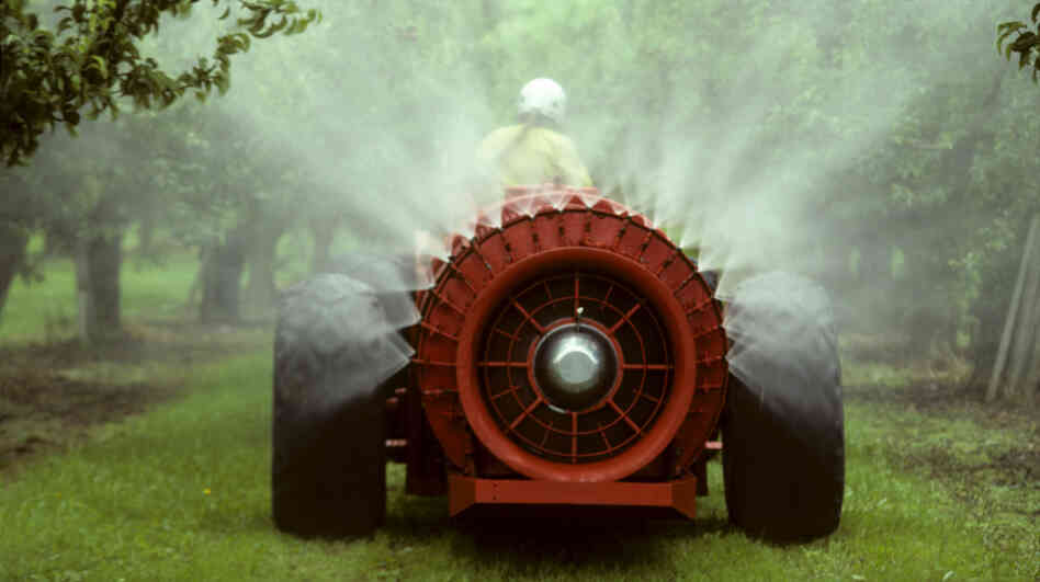 A pesticide sprayer rolls through an apple orchard.