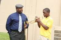 Antoine Batiste (Wendell Pierce) instructs his young band student in Treme, played by Jaron Williams.