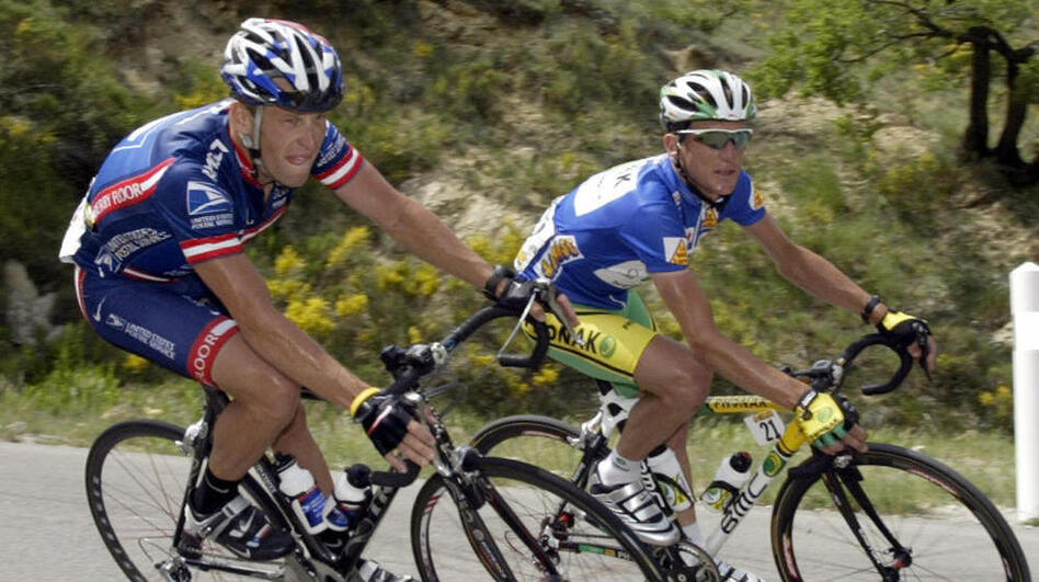 "Lance Armstrong (L) rides close to compatriot Tyler Hamilton during the fifth stage of the ""56th Criterium du Dauphine Libere"" in June of 2004. (AFP/Getty Images)"