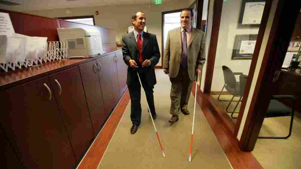 Attorney Richard Bernstein (left) and Angelo Binno walk through the law office of The Bernstein Law Firm in Farmington Hills, Mich., on May 24. Binno, who is legally blind, is suing the American Bar Association, saying its standards don't accommodate blind law school applicants.