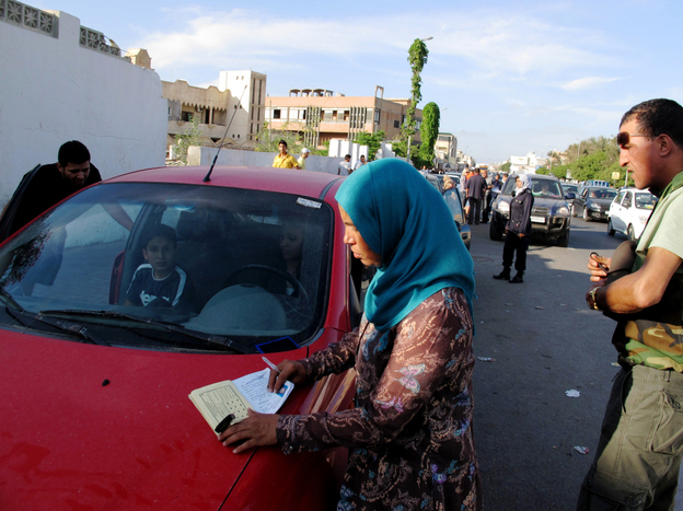 Volunteer Mabarka Mohammed al Mansouri, who manages the women-only gas station in Tripoli, checks the identification of one of the gas line patrons to make sure they haven't pumped gas in a week.