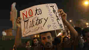 A man holds a placard protesting military trials at a demonstration in front of a building where the high military council met with youth groups on June 1.