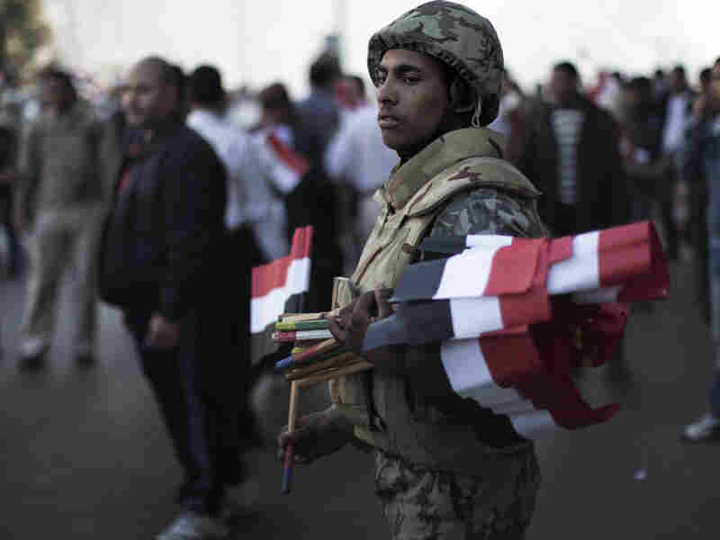 A soldier gives demonstrators flags on Feb. 18 as they enter Cairo's Tahrir Square for celebrations marking one week since Hosni Mubarak was forced from office. Goodwill between activists and the military has dwindled as some of Mubarak's practices of silencing critics continue.