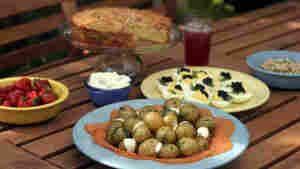 A misdsommar feast spread on a picnic table includes cake and strawberries, new potatoes and smoked salmon, shrimp salad and a special cocktail.
