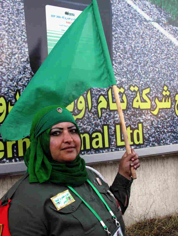 Volunteer Ibtisam Saadeddin, who wears a khaki uniform and a badge and pins with photos of Moammar Gadhafi, says she patrols the line at the women-only gas station to make sure no fights break out.