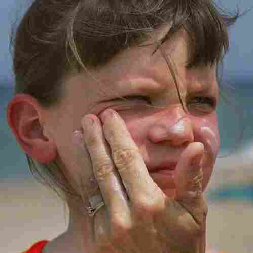 Savannah Stidham gets smeared with sunscreen during a visit to a beach in Fort Lauderdale, Fla., in 2006.