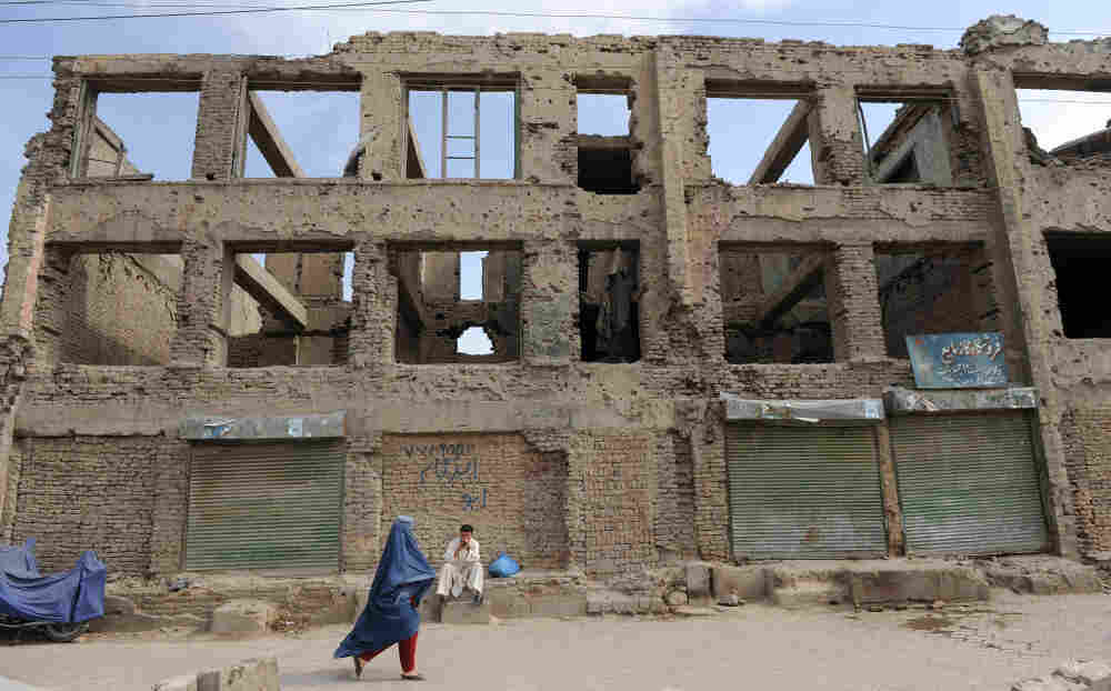 A burqa-clad Afghan woman walks past the ruins of a building destroyed during the civil war in Kabul. This picture was taken June 13.