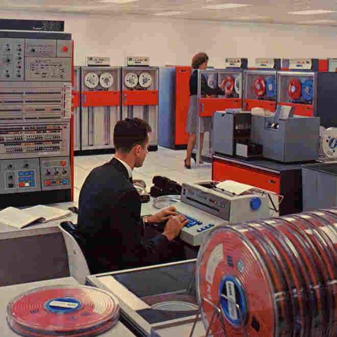 This is a 1964 IBM promotional handout photo of the System/360. A special IBM Selectric typewriter, being used by the man, would allow programmers to talk to the mainframe, left background.