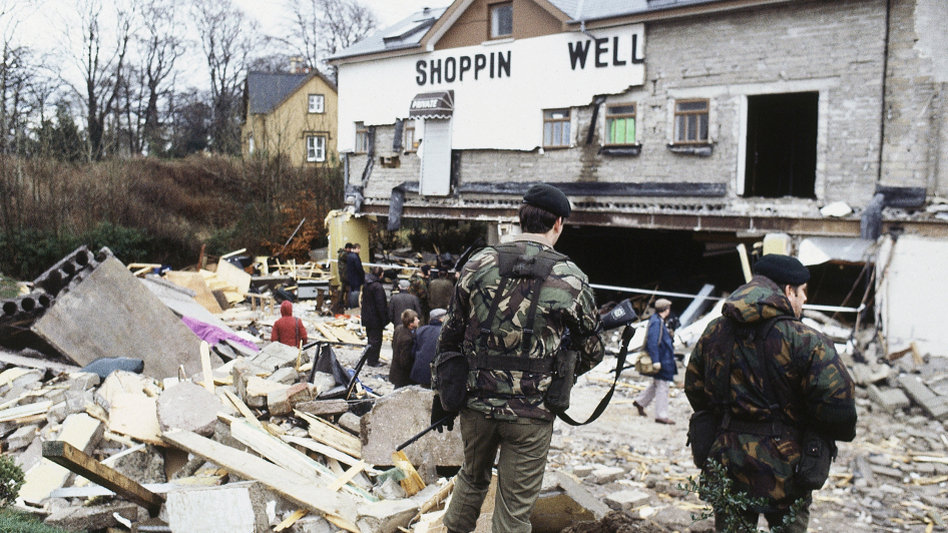 British troops survey the scene after a massive bomb, set up by the Irish National Liberation Army, destroyed a public house and disco in Northern Ireland in December 1982. Sixteen people died, including two British troops, and 60 others were injured.