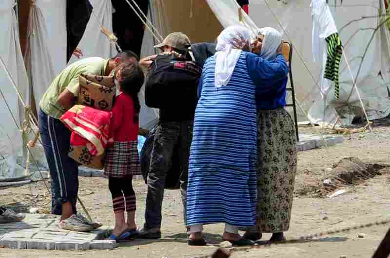 Syrian refugees greet each other at the Turkish Red Crescent camp in Hatay, Turkey, less than 2 miles from the Syrian border, on Wednesday.