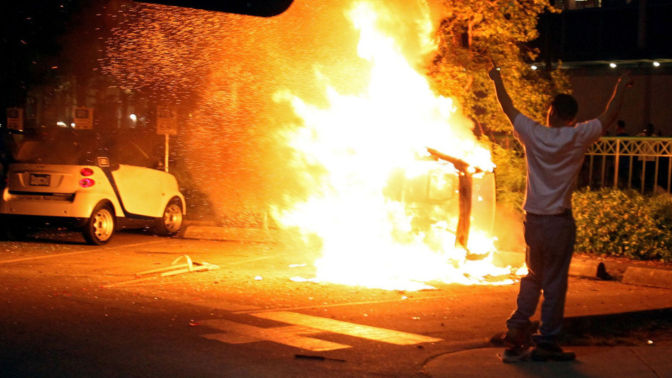 A person walks in front of a burning vehicle after riots break out following the Vancouver Canucks' loss in the NHL finals.