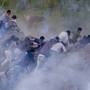 Pro-Palestinian protesters run from tear gas fired by Israeli troops along the border between Israel and Syria on June 5. Israeli troops battled hundreds of pro-Palestinian protesters who tried to burst across Syria's frontier with the Golan Heights, killing a reported 20 people and wounding scores more.