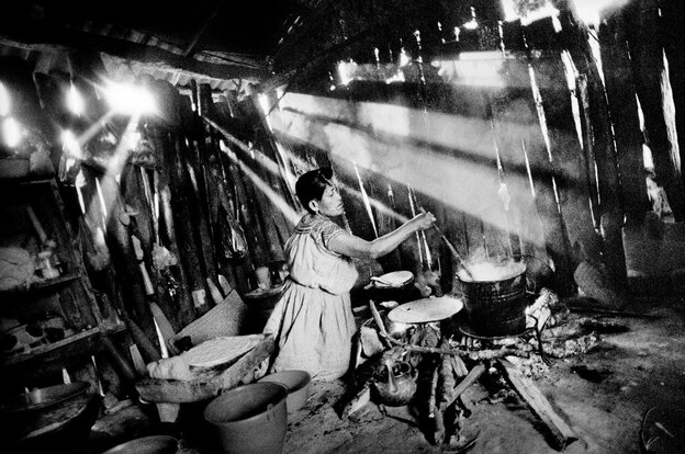 In the kitchen of her home, a woman boils corn to make tortillas,  San Miguel Cuevas, Mexico.