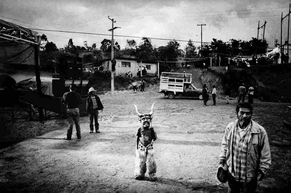 Dressed for ceremonial dancing, a boy awaits the start of his town's Saint's Day celebration, San Pedro Chayuco, Mexico.