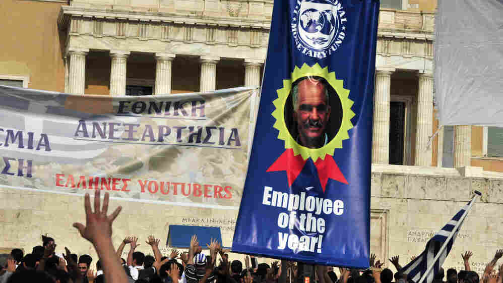 Protesters demonstrate in front of the Greek Parliament in Athens on Wednesday with a banner criticizing Prime Minister George Papandreou as an International Monetary Fund employee of the year.