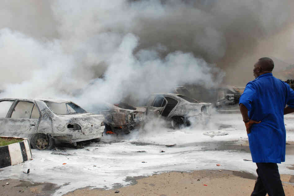 A man looks at burnt out cars,  at the parking lot of the police headquarters, following an explosion, in Abuja, Nigeria.