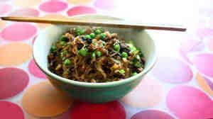 Chopsticks rest across a bowl of noodles on a placemat