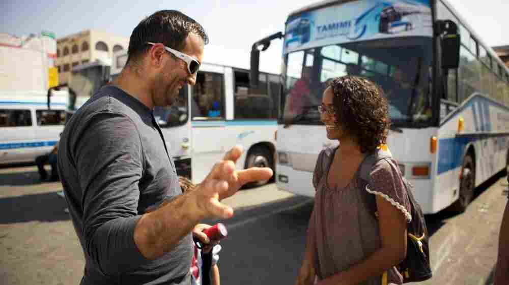 Palestinian artist Khaled Jarrar (left) has been stamping passports in advance of a possible Palestinian bid for recognition at the United Nations in September. His stamp is not a valid passport mark, but a statement in support of U.N. bid. Here, he stamps a tourist's passport at the Ramallah central bus station.
