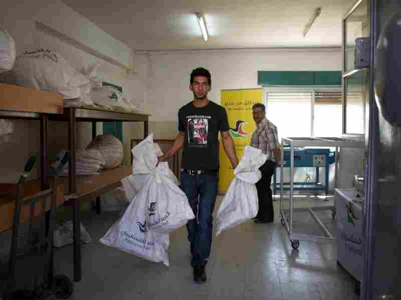 """A Palestinian postal worker carries mailbags out to trucks for delivery. In advance of a possible Palestinian drive for statehood at the U.N. in September, international mail now goes through Jordan instead of Israel. The post office also has new logo and slogan: """"We Emerge Again."""""""