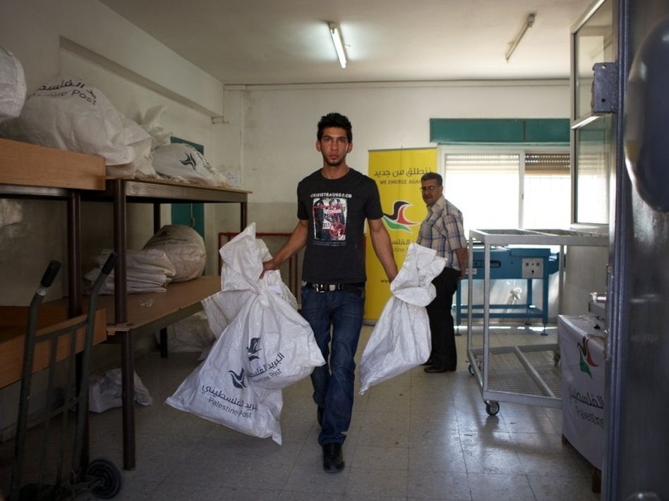 "A Palestinian postal worker carries mailbags out to trucks for delivery. In advance of a possible Palestinian drive for statehood at the U.N. in September, international mail now goes through Jordan instead of Israel. The post office also has new logo and slogan: ""We Emerge Again."""