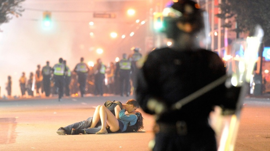 Vancouver riot police walk in the street as a couple kiss. (Getty Images)