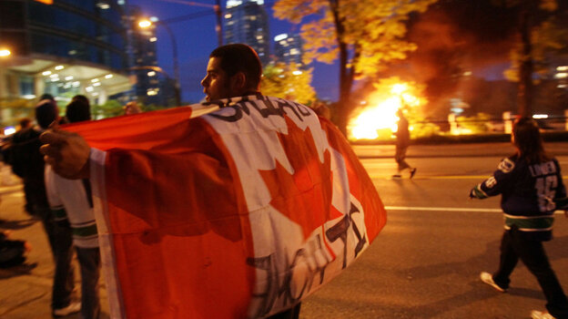 A man with a Candanian flag walked in front of a burning vehicle Wednesday night (June 15, 2011) in Vancouver, Canada.