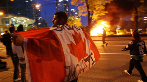 A man with a Candanian flag walked in front of a burning vehicle Wednesday night (June 15, 2011) in Vancouver, Canada. (Getty Images)