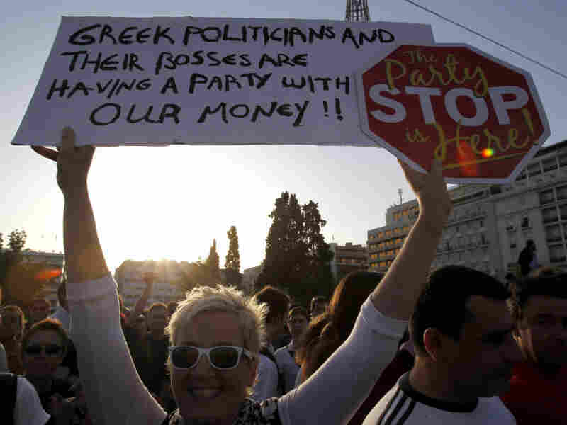 A protester holds a banner in front of the Greek Parliament during a peaceful rally in central Athens, May 25, 2011.