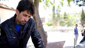 Syrian activist Mohammed Feezo, 32, with his laptop in the village of Guvecci in southeastern Turkey,  overlooking the Syrian border. He brought his wife and children here for safety, but intends to return to Syria  to continue the uprising against the government.