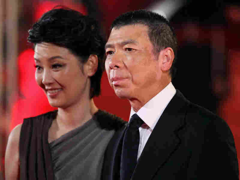 Director Feng Xiaogang, whose 2010 film Aftershock is China's highest-grossing Chinese-made film of all time, arrives at the 14th Shanghai International Film Festival. At left is his wife Xu Fan, who starred in Aftershock.