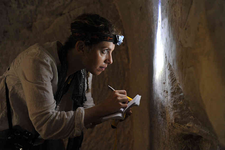 Archaeologist Karen Stern transcribes and measures a newly discovered graffito, in ancient Greek, in a burial cave in the Judean foothills of Israel. The cave is impossible to locate with the naked eye and requires an initial descent via fig tree.