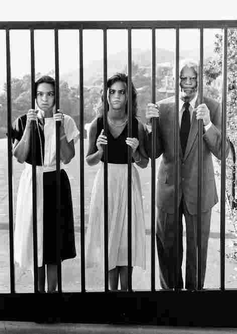 Barbara, Jennifer and Cary Grant make faces through the gate of their Beverly Hills home.
