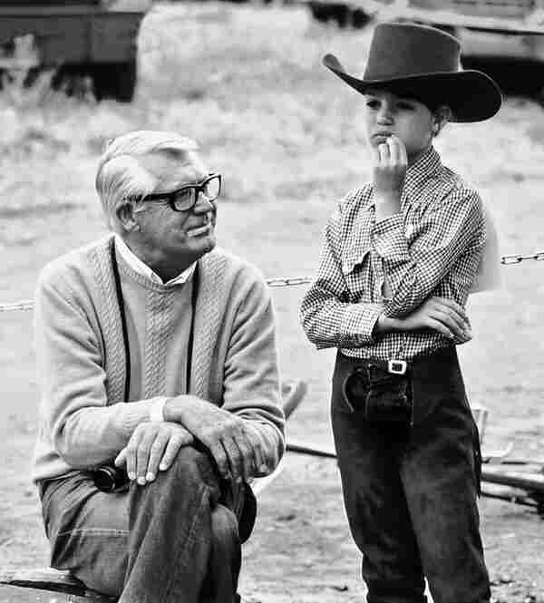 Cary Grant wears one of his signature camel-colored cashmere sweaters to Jennifer's horse show in Malibu, Calif.