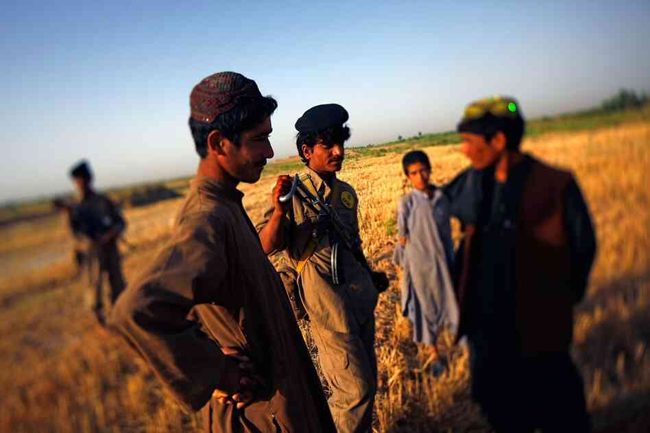 A local farmer watches as Isutalah (center) patrols with the Marines. The ISCI forces are selected by tribal elders, paid $150 per month and given uniforms. The benefit, say Marine officers, is that they know the local people — and who is and is not a member of the Taliban.