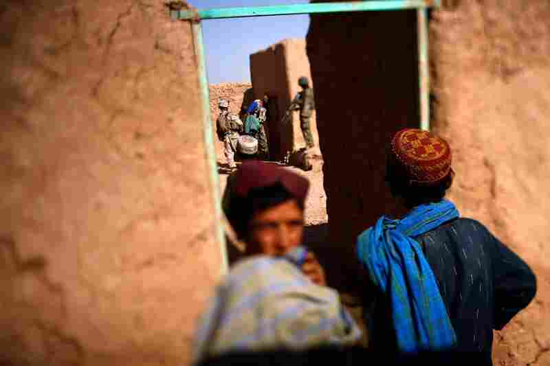 Afghan children watch from a doorway as Marines and Afghan National Army soldiers search a compound in a new area of operation in Marjah.