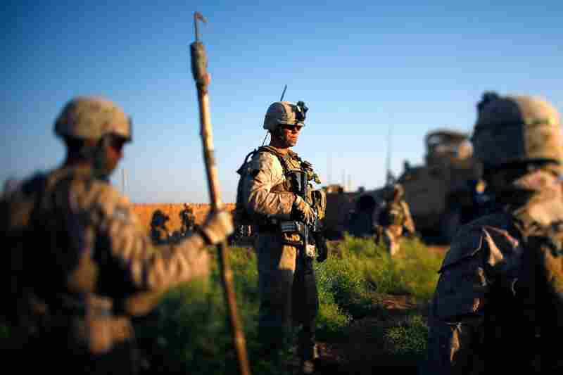 Marines pause during a clearing operation with local security forces in a new and unchecked area of Marjah.